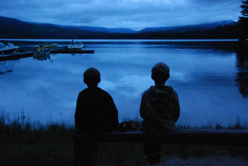 two kids in front of the lake at twilight