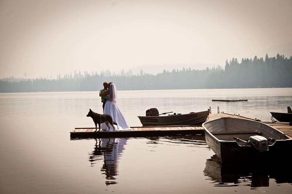 Wedding couple and dog on dock.